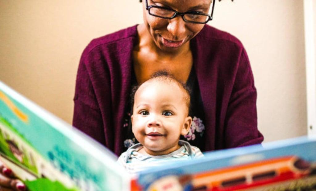 Bebé sentado en el regazo de la madre leyendo un libro