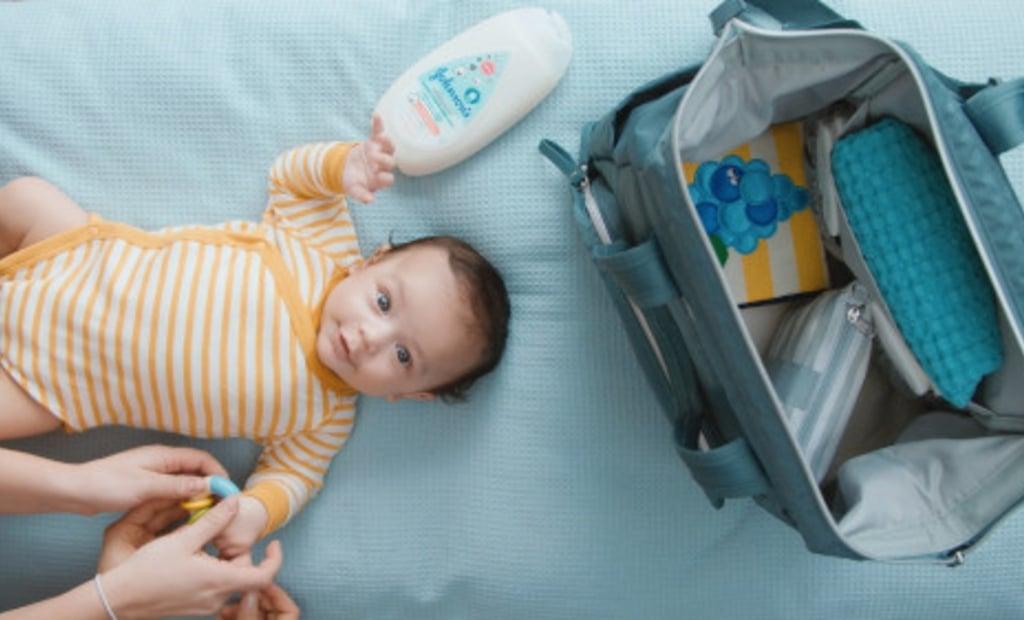 Niño acostado en la cama junto a bolso de viaje