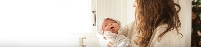 Mujer que sostiene a un bebé recién nacido envuelto en una toalla