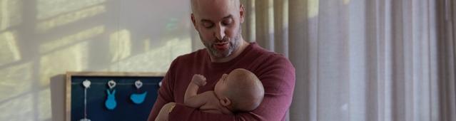 Papá acunando a su bebé para hacerlo dormir