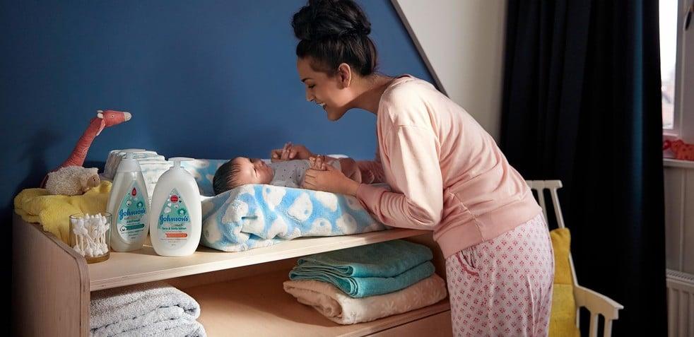 Mamá y bebé en el cuarto con productos para bebé JOHNSON'S®