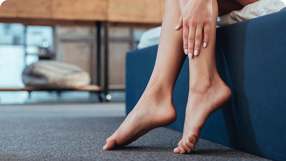 Una mujer que se aplicaloción para bebéJohnson's® en las piernas