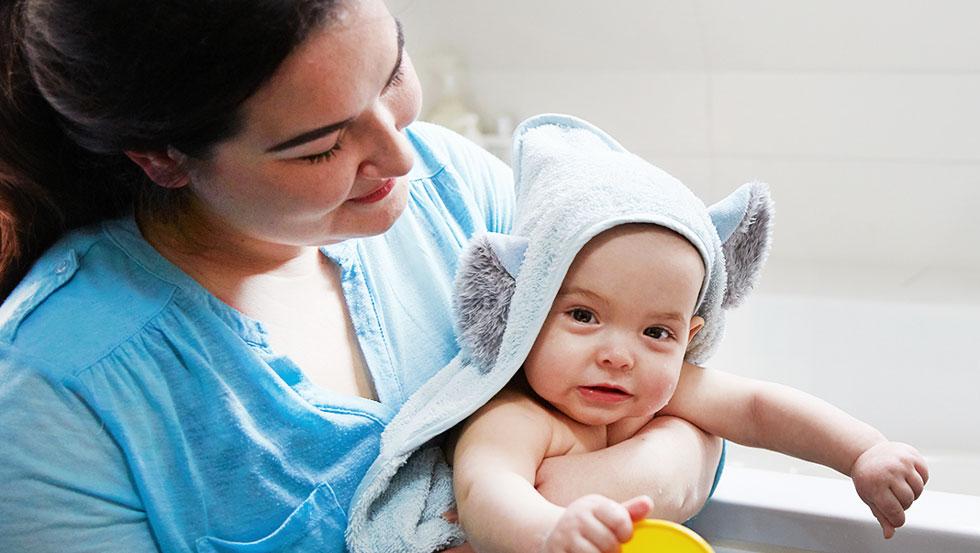 Madre acunando a su bebé y secándolo después del baño