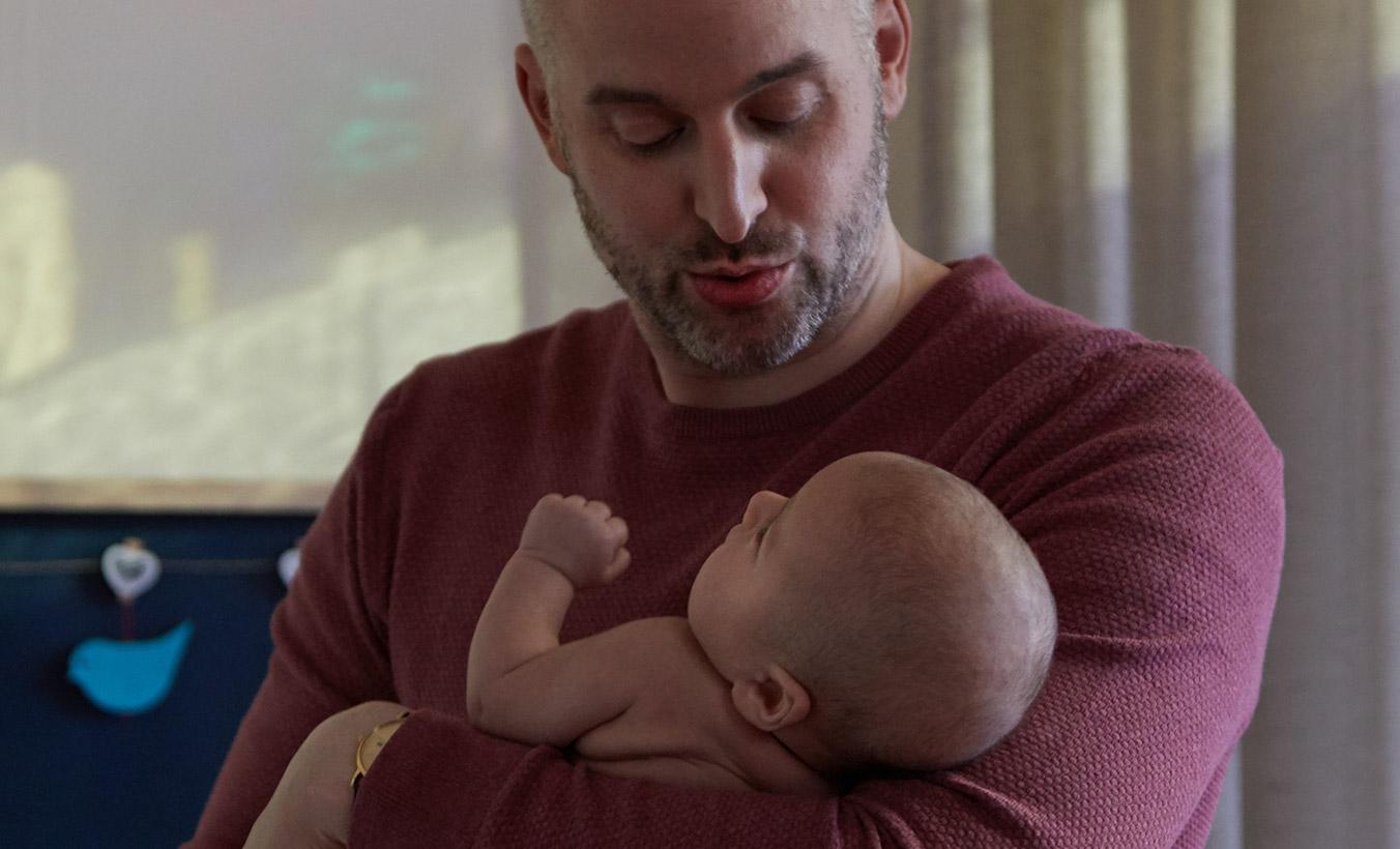 papá haciendo dormir a su recién nacido
