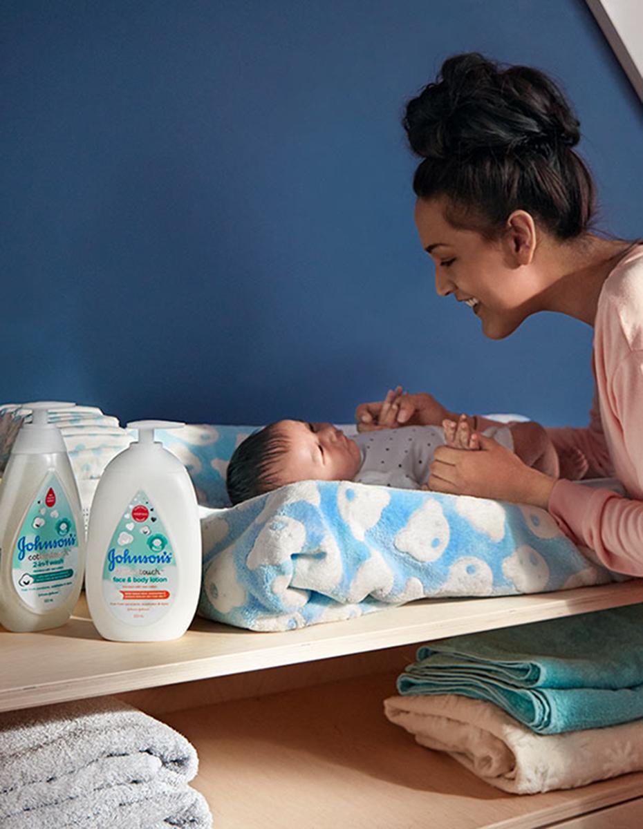Una madre con su bebé usando los productos para recién nacidos Johnson's® CottonTouch™