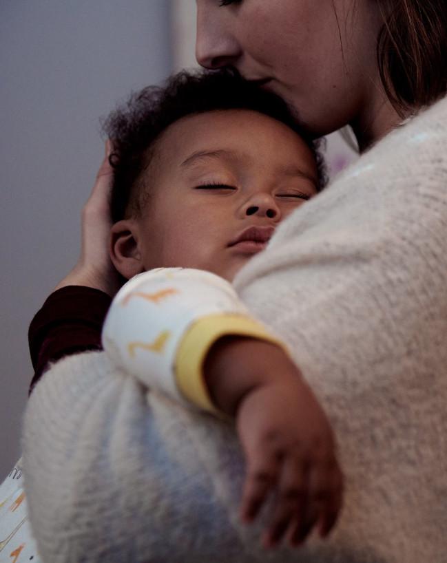 mamá sosteniendo a bebé dormido