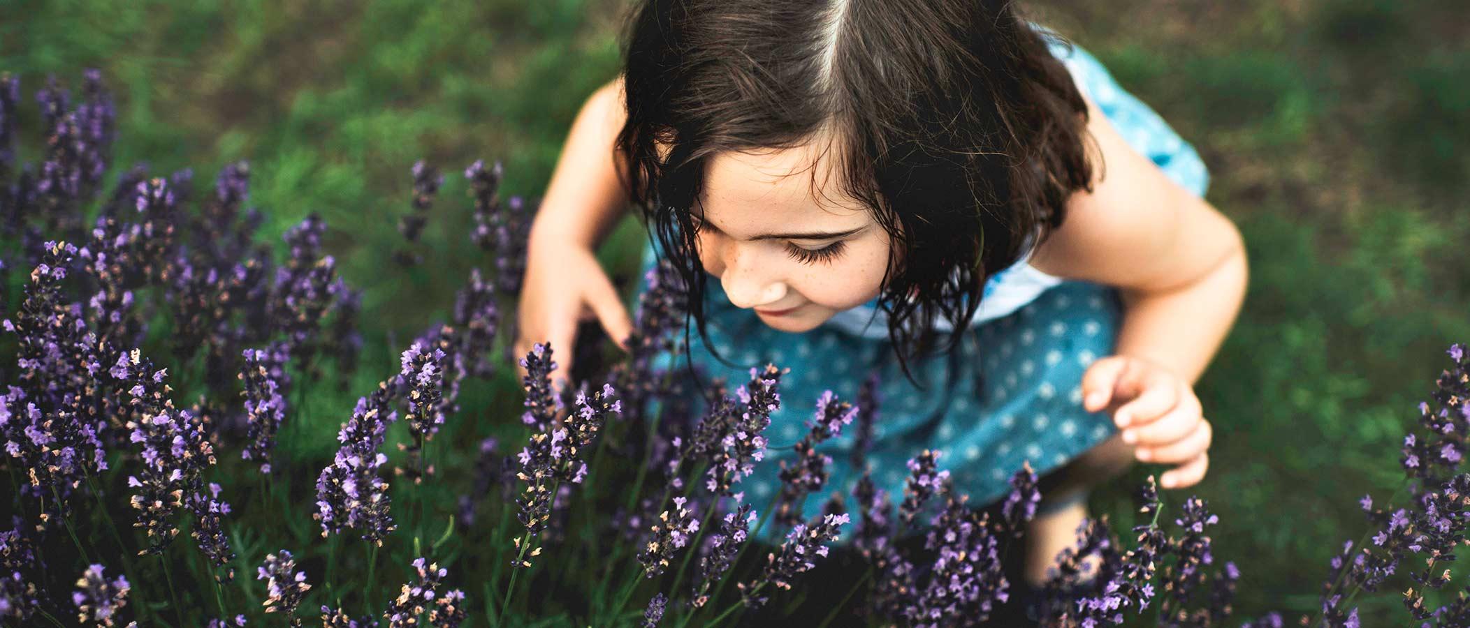 Niña pequeña oliendo flores
